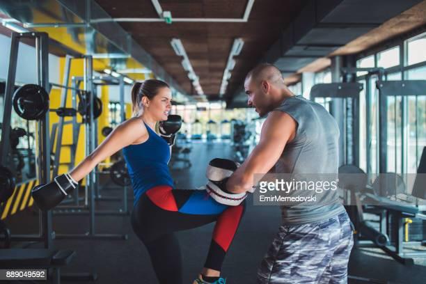 mujer haciendo entrenamiento de kickboxing con su entrenador - artes marciales fotografías e imágenes de stock