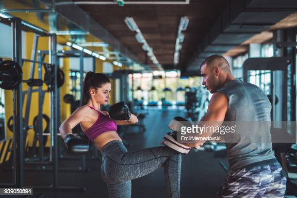 woman doing kickboxing workout with her coach - self defence stock pictures, royalty-free photos & images