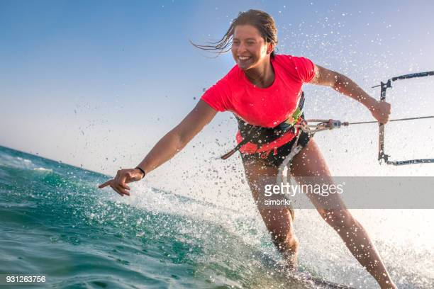 woman doing kitesurfing - three quarter length stock pictures, royalty-free photos & images