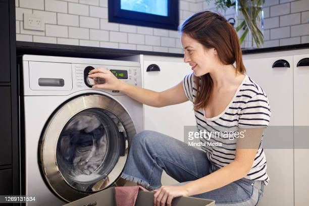 woman doing laundry - washing machine stock pictures, royalty-free photos & images