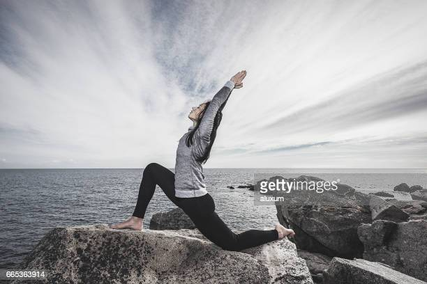 woman doing low lunge yoga pose at the sea - yogi stock photos and pictures