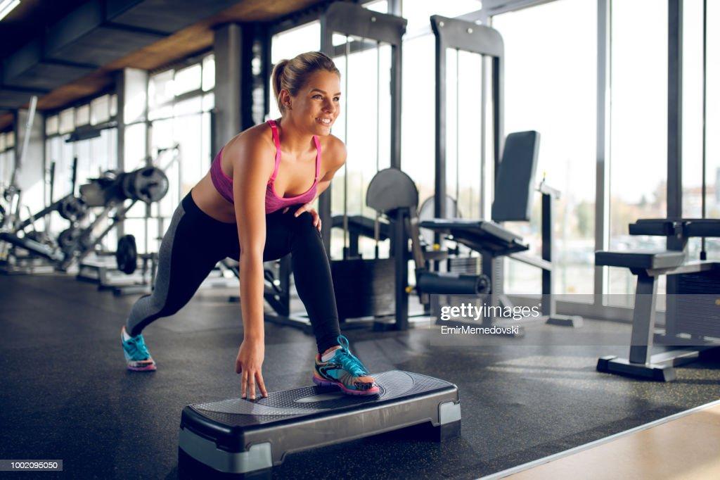 婦女做刺在臺階健美操設備在健身房 : 圖庫照片