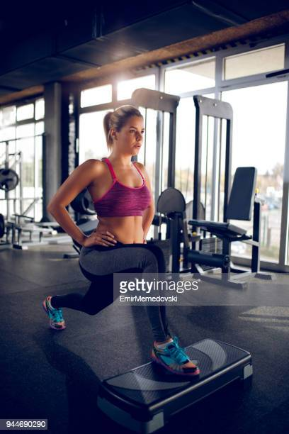 Femme faisant des mouvements brusques sur matériel d'aérobic step au gymnase