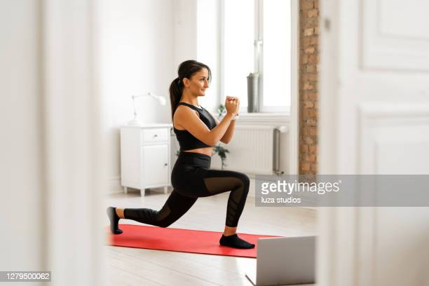 woman doing lunges while watching exercise tutorials - mid adult women stock pictures, royalty-free photos & images