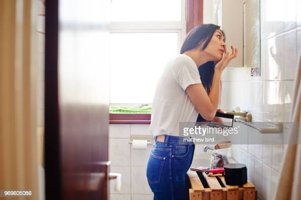 woman doing make-up in bathroom mirror - vanity stock pictures, royalty-free photos & images