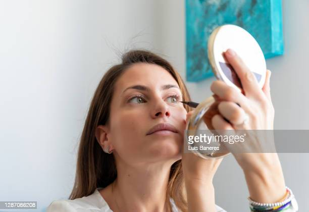 woman doing makeup of eyes at home - アイライナー ストックフォトと画像