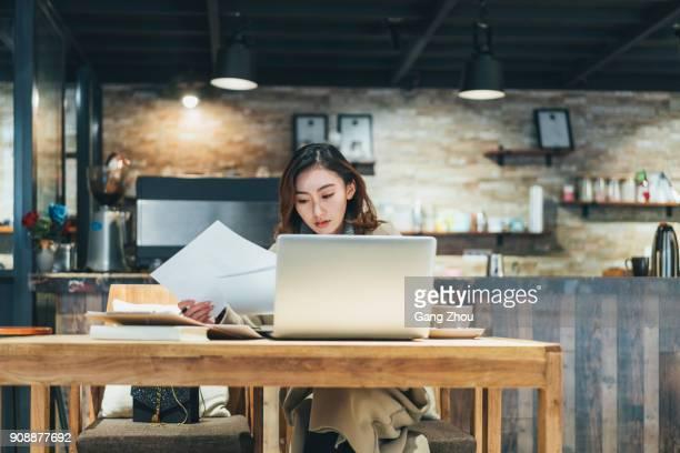 vrouw doet papierwerk met laptop in de coffeeshop - freelancer stockfoto's en -beelden