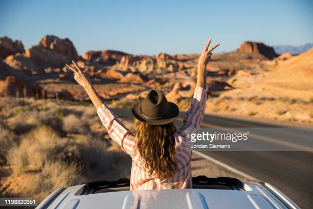 a woman doing peace signs out the sunroof of a car - las vegas stock pictures, royalty-free photos & images