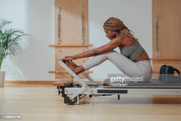 woman doing pilates exercise on reformer - pilates stock pictures, royalty-free photos & images