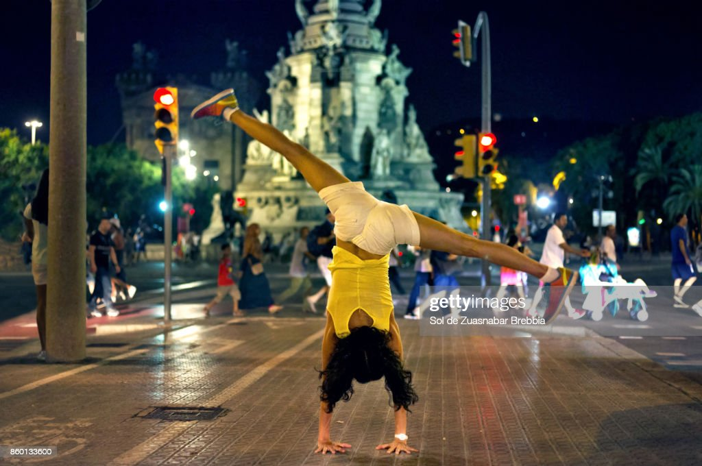 Woman doing pirouettes on her arms in the streets of barcelona. : Stock Photo