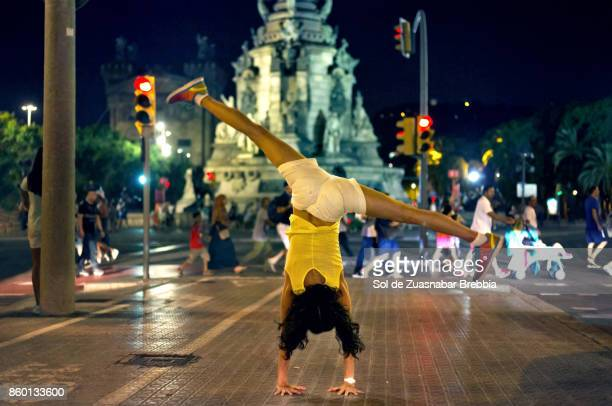 Woman doing pirouettes on her arms in the streets of barcelona.
