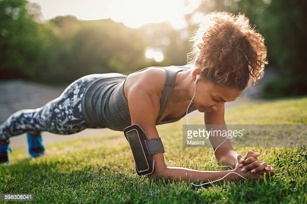 Woman doing plank exercise on grassy field at park