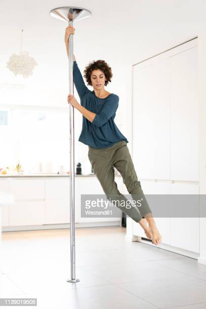 woman doing pole dance at home - pole dance photos et images de collection