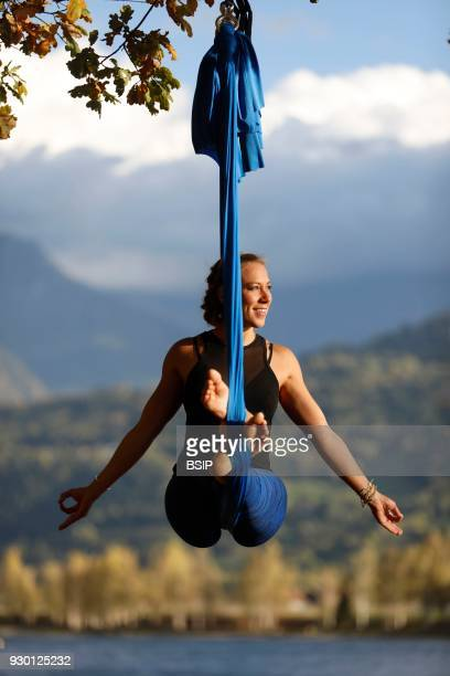 Woman doing pose of aerial yoga using hammock outdoors SaintGervais France