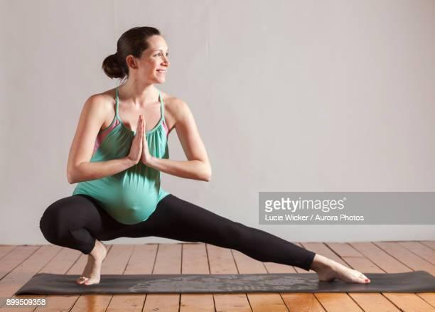 Woman doing Prenatal Yoga side lunge, Boston, Massachusetts, USA