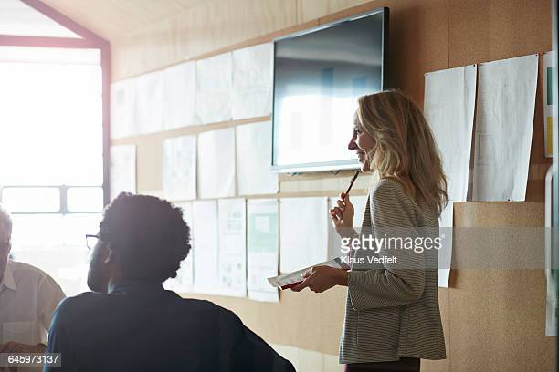 woman doing presentation, using tablet & screen - employee engagement stock pictures, royalty-free photos & images