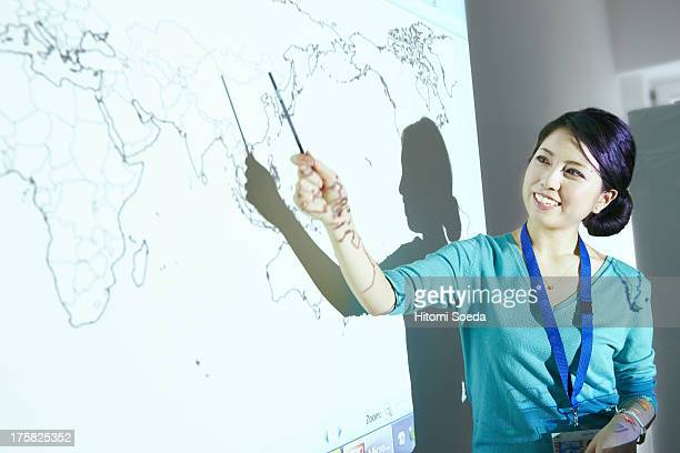 Woman doing presentation with world map projected on wall