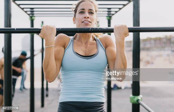 Woman Doing Pull-Ups on Monkey Bars for Fitness