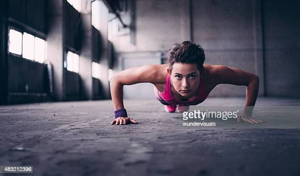 Woman doing push ups with determination in  industrial space