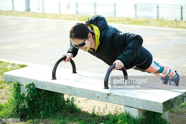 Woman doing push-ups on bench