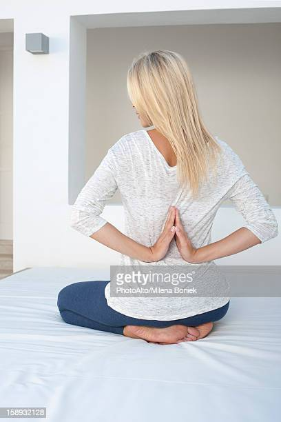Woman doing reverse prayer position on bed, rear view