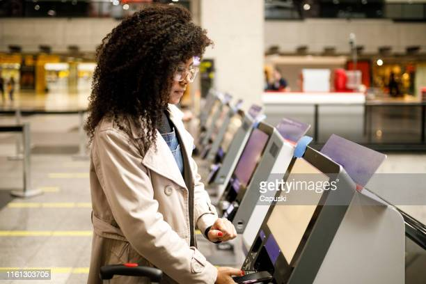 woman doing self check in at the airport with mobile phone - airplane ticket stock pictures, royalty-free photos & images
