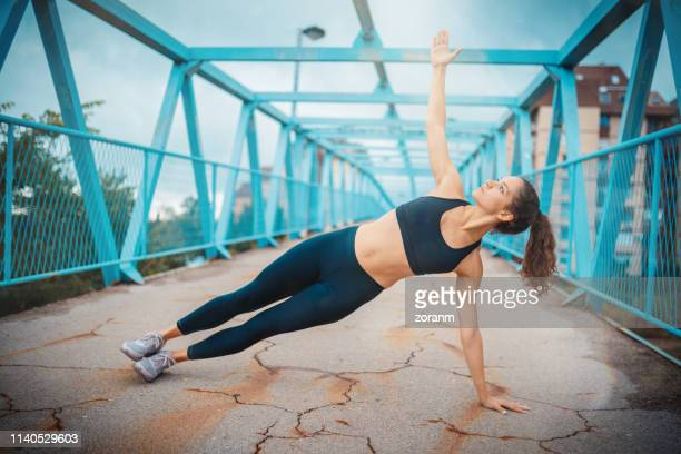 woman doing side plank pose - plank exercise stock pictures, royalty-free photos & images