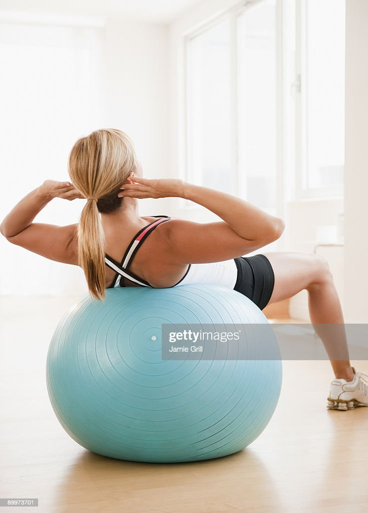 Woman doing sit up on exercise ball : Bildbanksbilder