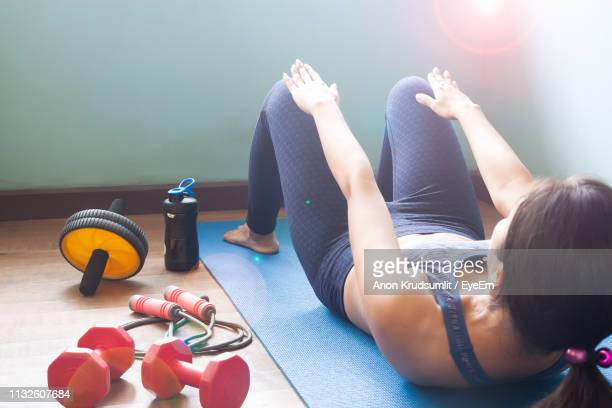 woman doing sit-ups on exercise mat at home - home workout stock pictures, royalty-free photos & images