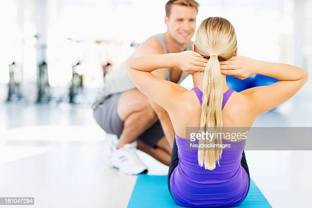 Woman Doing Sit-Ups While Instructor Assisting Her In Gym