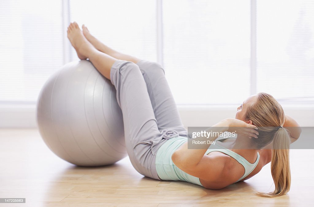 Woman doing sit-ups with fitness ball : Stock Photo