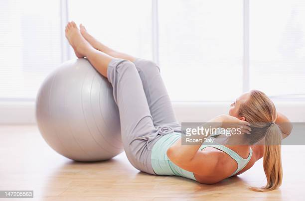 woman doing sit-ups with fitness ball - fitness ball stock pictures, royalty-free photos & images