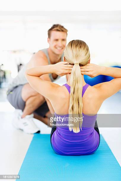 Woman Doing Sit-Ups With Instructor Smiling In Gym