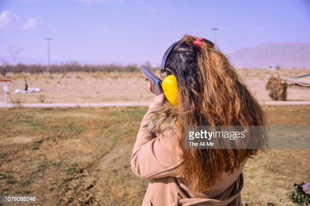 a woman doing skeet shooting - gun control stock pictures, royalty-free photos & images