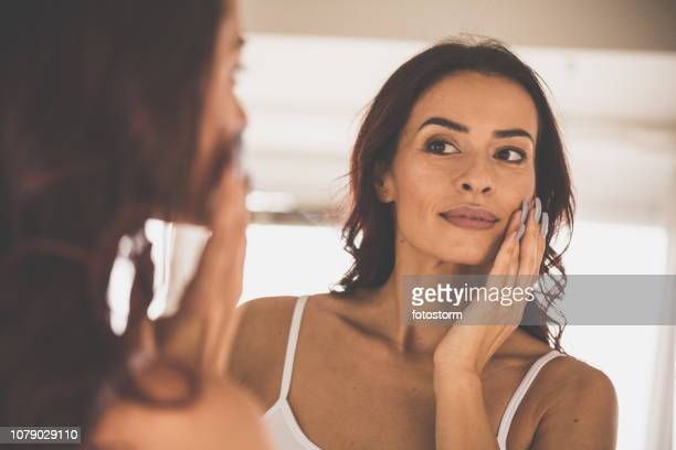 woman doing skin care routine at home - mid adult women stock pictures, royalty-free photos & images