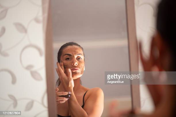 woman doing skin mask in front of mirror - exfoliation stock pictures, royalty-free photos & images