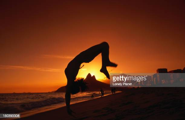 Woman doing somersault on beach at sunset.