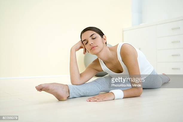 Woman doing split, holding head, eyes closed