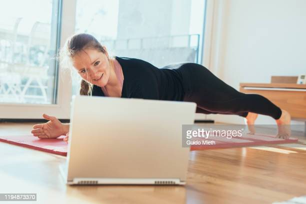 woman doing sport in front of laptop. - sporting term stock-fotos und bilder