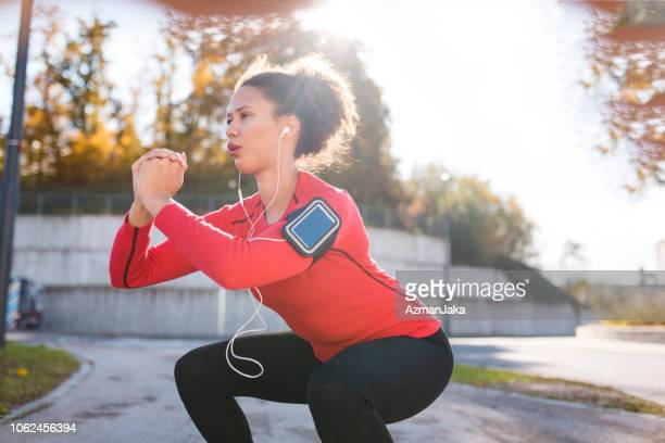 woman doing squats - squatting position stock pictures, royalty-free photos & images