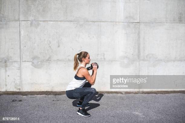 Femme faisant des squats avec un kettlebell