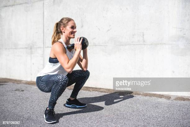 woman doing squats with a kettlebell - weight stock pictures, royalty-free photos & images