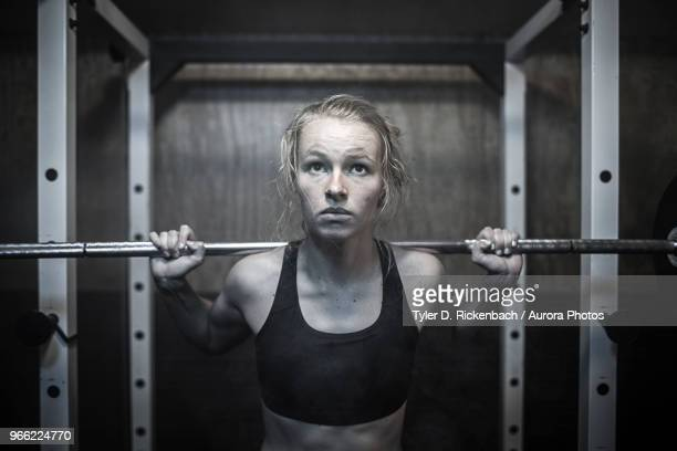 woman doing squatting exercise with barbell in gym - sports bra stock pictures, royalty-free photos & images