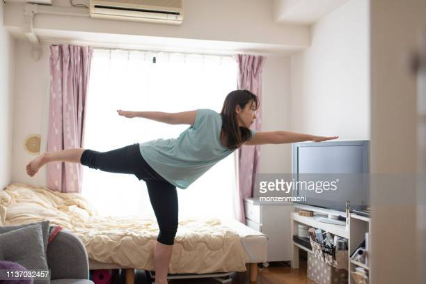 woman doing stretches on bed in the morning - only japanese stock pictures, royalty-free photos & images