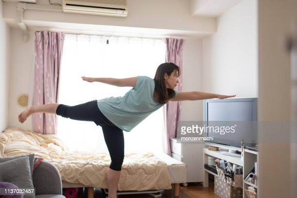 朝のベッドでストレッチをしている女性 - 日本人のみ ストックフォトと画像