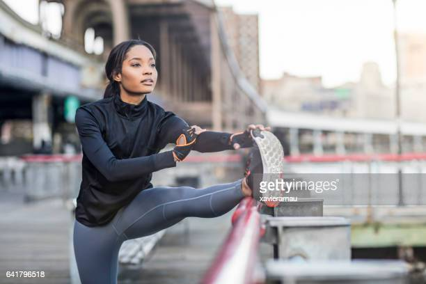 woman doing stretching exercise by railing in city - sports clothing stock pictures, royalty-free photos & images