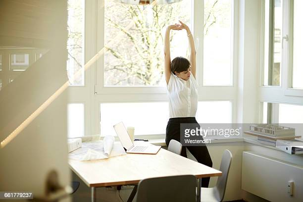 woman doing stretching exercise in her office - 女性建築家 ストックフォトと画像