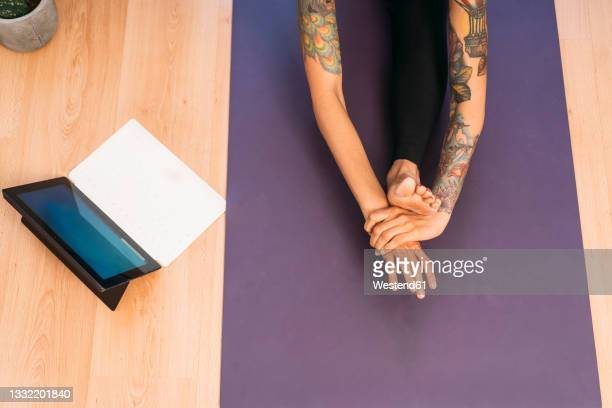 woman doing stretching exercise while e-learning through laptop at home - %e... ストックフォトと画像