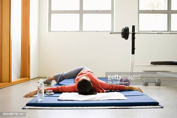 Woman doing stretching exercises on mat in gym