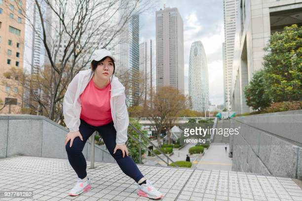 woman doing stretching in city - fat asian woman stock pictures, royalty-free photos & images